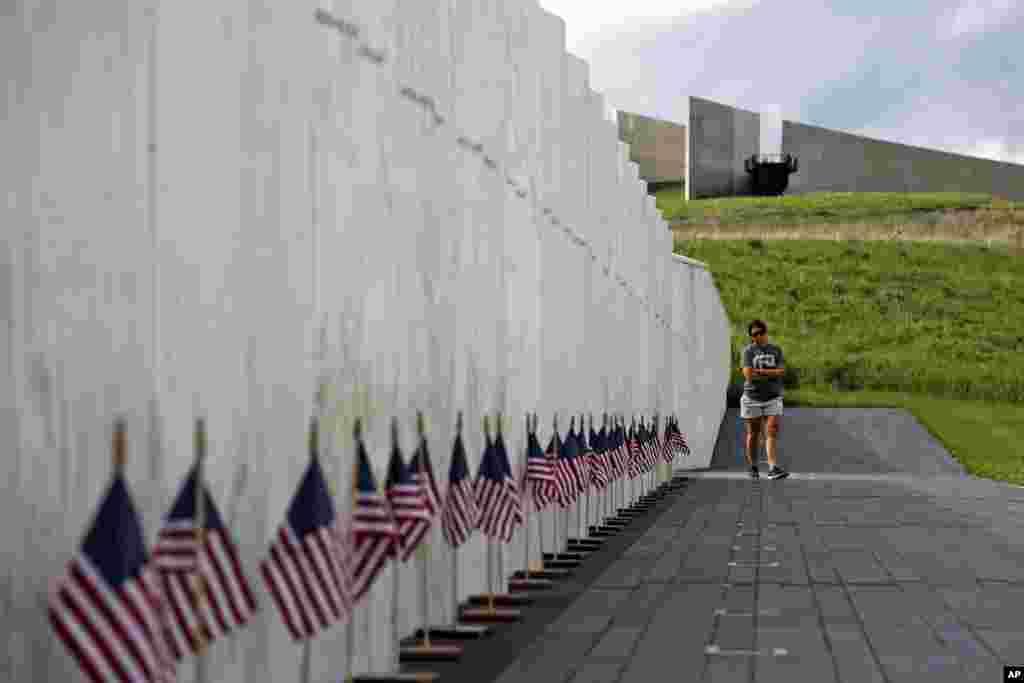 Una visitante al Flight 93 National Memorial hace una pausa en el Muro de los Nombres que contiene los nombres de los 40 pasajeros y tripulantes del vuelo 93 de United que fueron asesinados en este campo el 11 de septiembre de 2001, el 31 de mayo de 2018. (Foto AP / Gene J. Puskar)