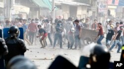 Garment workers throw objects at riot police during a strike near a factory of Canadia Center, on the Stung Meanchey complex at the outskirt of Phnom Penh, Cambodia, Friday, Jan. 3, 2014. Police wounded several striking Cambodian garment workers Friday when they opened fire to break up a labor protest, witnesses said.(AP Photo/Heng Sinith)