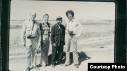 The black and white group photograph shows Richard Dudman (far left), Malcolm Caldwell (far right) and Elizabeth Becker (center left), with Commander Pin (center right), a senior Khmer Rouge military figure, near the eastern border with Vietnam preparing for war. (Courtesy photo of Elizabeth Becker)