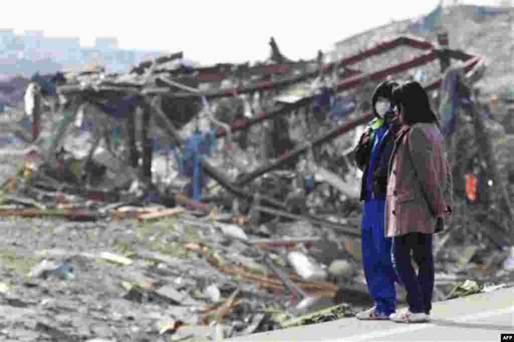 People look at a devastated area of Minamisanriku, northern Japan, Monday, March 14, 2011, three days after a powerful earthquake-triggered tsunami hit the country's east coast. (AP Photo/The Yumiuri Shimbun, Tsuyoshi Matsumoto) JAPAN OUT, CREDIT MANDATOR