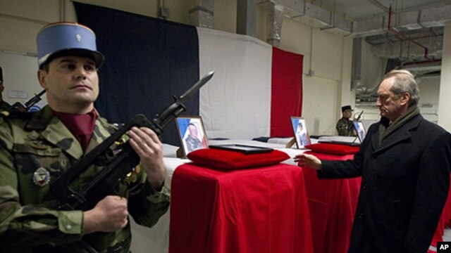 French Defense Minister Gerard Longuet (R) stands in front of the four coffins of French soldiers to pays his respects during a ceremony at Kabul Airport in Kabul on January 21, 2012.