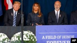 President Donald Trump, left and first lady Melania Trump, center, and Pennsylvania Governor Tom Wolf, listen as the names of the 44 people who died in the crash of Flight 93 are read during the September 11th Flight 93 Memorial Service in Shanksville, Pa