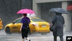 Watu wakitembea katika mvua kwenye mtaa wa Lexington Avenue mjini New York City wakati kimbunga Irene kinaelekea mwambao wa mashariki, August. 27, 2011