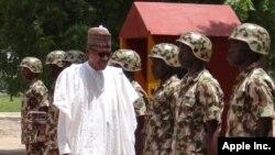 FILE - Nigerian President Muhammadu Buhari reviews troops in Maiduguri, Oct. 1, 2017.