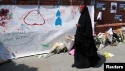 Žena stoji ispred panoa sa porukama, koji je zakačen na zidu u blizini mesta gde se odigrao napad kod džamije u Finsburi parku