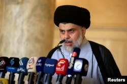 FILE - Iraqi Shi'ite cleric Muqtada al-Sadr delivers a sermon to worshippers during Eid al-Fitr prayers at the Kufa mosque near Najaf, June 5, 2019.