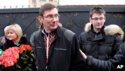 Former Ukrainian Interior Affairs Minister Yuri Lutsenko walks out of his prison to be greeted by his wife, left, and son.