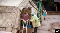 Seorang petugas kesehatan membersihkan tangannya sebelum memasuki tenda penyaringan Ebola di rumah sakit di Kenema, Sierra Leone (11/8). (AP/Michael Duff)