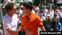 Le Britannique Andy Murray, à gauche, félicite Novak Djokovic de la Serbie a remporté la demi-finale du l' Open français du tennis en cinq sets 6-3, 6-3, 5-7, 5-7, 6-1, au stade Roland-Garros, à Paris, France, 6 Juin, 2015. (AP Photo / David Vincent)