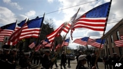 U.S. Marine Corps ROTC carry flags during a Veteran's Day parade Friday, Nov. 11, 2011 in Media, Pa. (AP Photo/Alex Brandon)