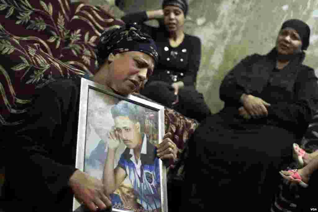 A woman holds a photo of her son, a Coptic man who was killed during a terror attack in 2016, as the man's sister and aunt cry during his funeral in Cairo, Egypt. Terror attacks targeting Copts increase near their Christmas on Jan. 7.