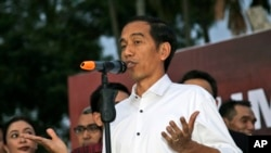 FILE - Indonesian president-elect Joko Widodo gestures as he speaks to his supporters during a gathering in Jakarta.