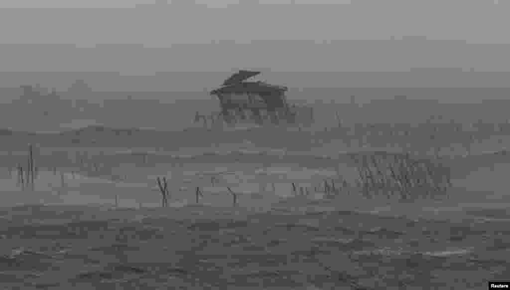 Rumah panggung milik nelayan di tengah laut miring dihantam ombak, angin kencang dan hujan yang dibawa Topan Rammasun yang menghantam kota pesisir Bacoor, di Cavite, barat daya Manila (16/7). (Reuters/Erik De Castro)
