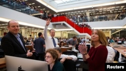 FILE - With Executive Editor Jill Abramson, right, publisher Arthur Sulzberger Jr. holds up four fingers to indicate the four Pulitzer Prizes won by the New York Times, as winners for the 2013 Pulitzer Prize are announced in the newsroom in New York.