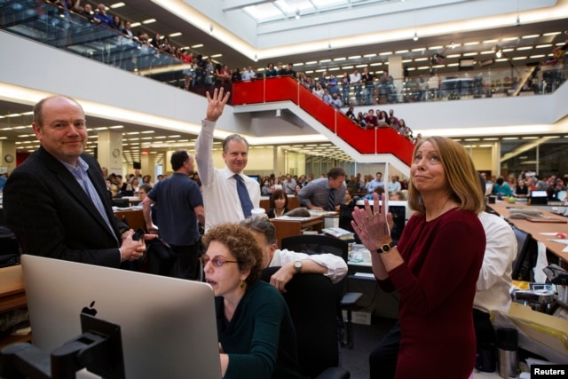 FILE - With Executive Editor Jill Abramson (R), publisher Arthur Sulzberger Jr. holds up four fingers to indicate the four Pulitzer Prizes won by the New York Times, as winners for the 2013 Pulitzer Prize are announced in the newsroom in New York.