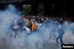Manifestantes são afastados com gás pelas forças de segurança, durante um protesto da oposiºão em Caracas, capital da Venezuela, 6 de Abril, 2017.
