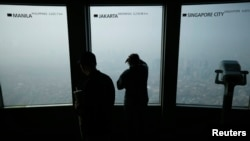 "A woman looks at central Seoul shrouded in heavy haze at an observation platform at ""N Seoul Tower"" located atop Mt. Namsan in central Seoul, Feb. 27, 2014."
