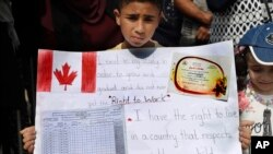 A Palestinian refugee boy holds a placard showing his school report card as hundreds of refugees request asylum at a rally outside the the Canadian Embassy, in Beirut, Lebanon, Sept. 5, 2019.