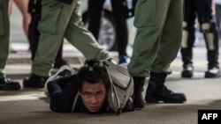 Polícia de choque detém indivíduo durante protestos contra nova lei de segurança nacional em Hong Kong (Fotode DALE DE LA REY / AFP)