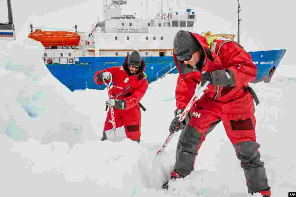 This image taken by expedition doctor Andrew Peacock shows scientists from the University of New South Wales in Australia, Ziggy Marzinellia and Graeme Clark, preparing a suitable surface for a helicopter landing next to the MV Akademik Shokalskiy (background), still stuck in the ice off East Antarctica.