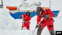 Para ilmuwan dari University of New South Wales di Australia, Ziggy Marzinellia dan Graeme Clark, menyiapkan landasan pendaratan helikopter di atas es di Antartika.