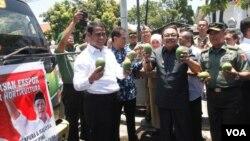 Menteri Pertanian Andi Amran Sulaiman dan Gubernur Jawa Timur Soekarwo melepas truk pengangkut komoditas pertanian dan hortikultura Jawa Timur ke sejumlah negara di Asia (foto: Petrus Riski/VOA).