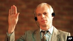 FILE - In this Monday, Nov. 24,1997 file photo. Polish immigrant and convicted killer Janusz Walus is sworn in during a Truth and Reconcilliation Commission hearing in Mamelodi, South Africa.