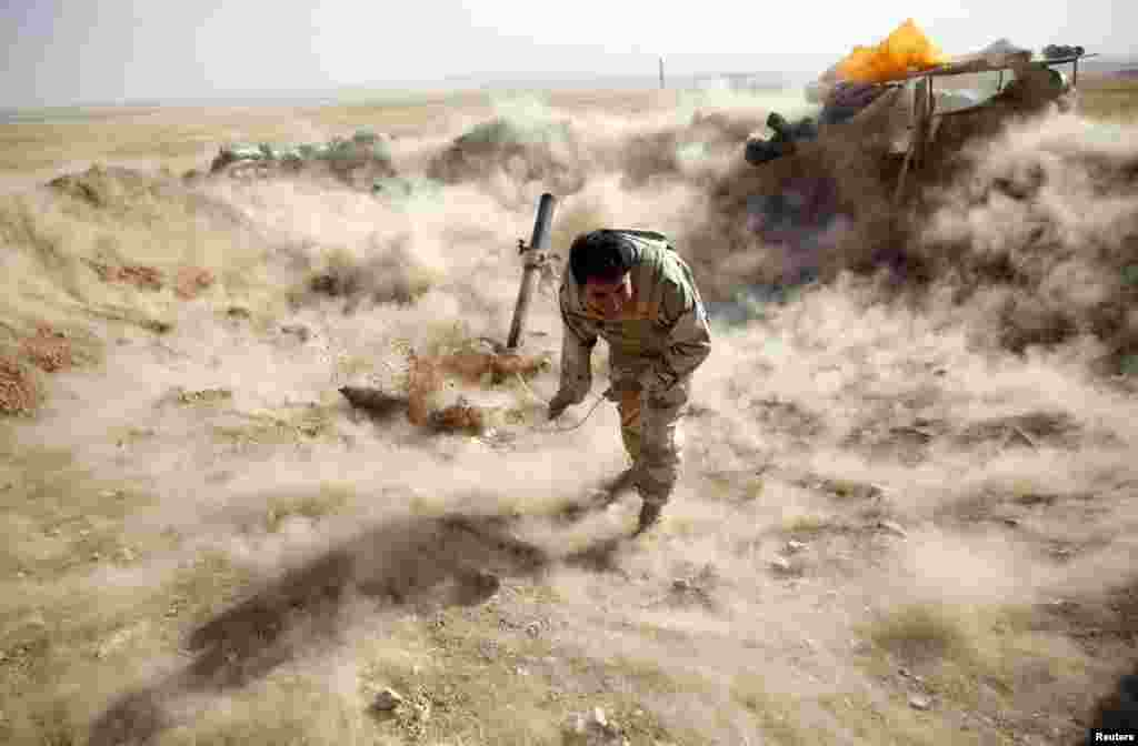 A Kurdish Peshmerga fighter launches mortar shells towards Zummar, controlled by Islamic State (IS), near Mosul, Iraq.