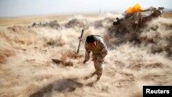یک پیشمرگه کرد در حال شلیک خمپاره به منطقه تحت کنترل شورشیان داعش در نزدیکی موصل - ۲۴ شهریور ۱۳۹۳