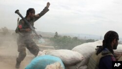 FILE - An Afghan National Army soldier, left, shouts against the Taliban, after firing a rocket towards Taliban positions, on the outskirts of Kunduz, northern Afghanistan, April 16, 2016.