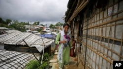 In this Aug. 27, 2018, photo, Rahima Akter walks through Balukhali refugee camp in Bangladesh. Rahima is a 19-year-old refugee who dreams of becoming the most educated Rohingya woman in the world. She recently finished high school and hopes to study human rights in college. (AP Photo/Altaf Qadri)