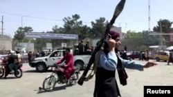 A Taliban fighter runs towards a crowd outside Kabul airport, Kabul, Afghanistan, Aug. 16, 2021, in this still image taken from a video. (REUTERS)