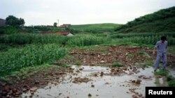 지난 1996년 8월 북한 은파군에서 폭우와 홍수에 무너져 떠내려온 건물 잔해가 농지를 덮었다.