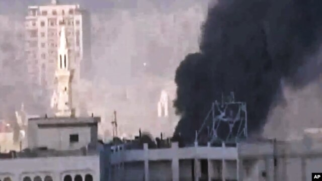 In this image made from amateur video released by the Shaam News Network and accessed May 30, 2012, purports to show black smoke leaping the air from shelling in Homs, Syria.
