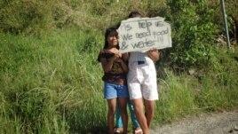 Children wait on roadsides hoping to get handouts from passing motorists, Cebu, Philippines, Nov. 15, 2013. (Steve Herman/VOA)