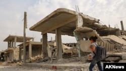 Qîzek li ber avahîyeke wêranbûyî li Kobanê