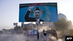 FILE - Afghan man shields himself from dust behind a billboard of Hamid Karzai.
