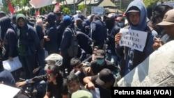 Seorang mahasiswa membawa kertas bertuliskan dukungan pengesahan RUU P-KS pada aksi di depan gedung DPRD Jawa Timur (foto Petrus Riski-VOA).
