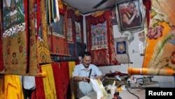FILE - A Tibetan artisan makes traditional wall decorations inside his workshop at Majnu Ka Tila, a Tibetan refugee camp in New Delhi, India, April 27, 2016.