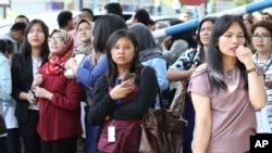 Orang-orang berkumpul saat mereka mengungsi setelah gempa kuat mengguncang Jakarta, Selasa, 23 Januari 2018. (AP Photo / Achmad Ibrahim)