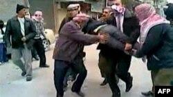 Demonstranti u jednom od predgrađa Damaska nose povređenog učesnika demonstracija,. Autentičnost snimka nije bilo moguće proveriti.