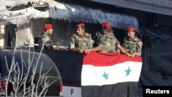 Soldiers loyal to the Syrian regime stand in a truck in Qusair after the Syrian army took control of the city from rebel fighters, June 5, 2013.