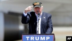 "Republican presidential candidate Donald Trump gestures to a his camouflaged ""Make America Great"" hat as he discuses his support by the National Rifle Association at a campaign rally at the Redding Municipal Airport, June 3, 2016, in Redding, California."