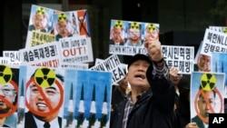 Người dân Nam Triều Tiên biểu tình ở thủ đô Seoul, Nam Triều Tiên, cầm ảnh của các cố lãnh đạo Bắc Triều Tiên, phản đối những vụ phóng phi đạn và những hành động khiêu khích mới đây của Bắc Triều Tiên, 15/4/14