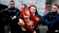 """Un activista del movimiento """"Femen"""", que protesta contra Le Pen, es conducida por la policía francesa en Henin-beaumont, en el norte de Francia, el domingo 7 de mayo de 2017."""