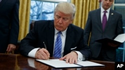 President Donald Trump signs an executive order to withdraw the U.S. from the 12-nation Trans-Pacific Partnership trade pact agreed to under the Obama administration, Monday, Jan. 23, 2017, in the Oval Office of the White House in Washington.
