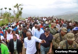 Haitian President Jovenel Moise, in white shirt, and Prime Minister Jack Guy Lafontant, in baseball cap, visited Jérémie, promising houses for people left homeless by a hurricane, March 31, 2017. (B. Magloire / VOA)