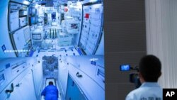 FILE - A worker monitors screens showing the interior of the Tianhe space station module after Chinese astronauts docked with and entered it at the Beijing Aerospace Control Center in Beijing, June 17, 2021.