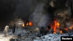 Men try to put out a fire at a market hit by air strikes in Idlib city, Syria June 12, 2016.