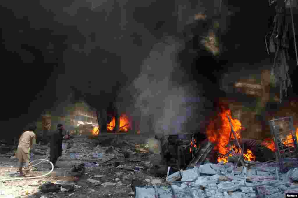 បុរសៗព្យាយាមពន្លត់អគ្គិភ័យនៅផ្សារមួយដែលទទួលរងការវាយប្រហារតាមអាកាសនៅក្នុងក្រុង Idlib ប្រទេសស៊ីរី កាលពីថ្ងៃទី១២ ខែមិថុនា ឆ្នាំ២០១៦។